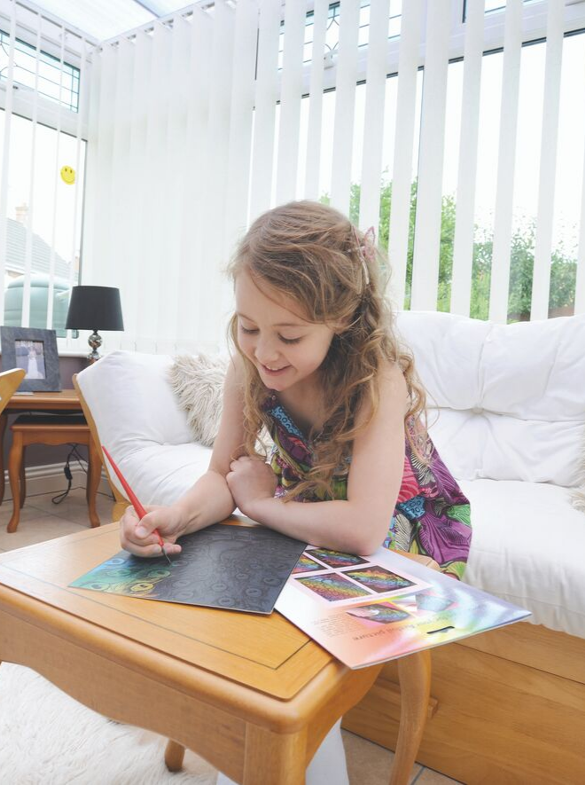 A girls creating scratch art picture
